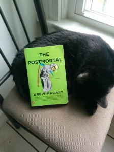 The Postmortal, in paperback, with Bagheera (an avid reader cat)